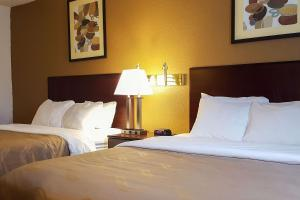 A bed or beds in a room at Quality Inn Ozark