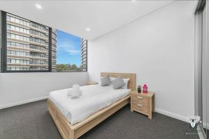 A bed or beds in a room at Kozy Olympic Park 2Bed APT + FREE PARKING