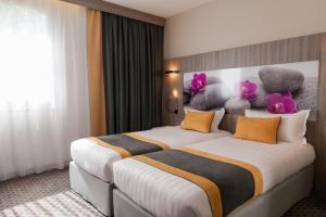 A bed or beds in a room at Clos St Eloi, The Originals Relais (Relais du Silence)