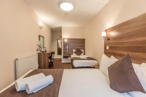 A bed or beds in a room at Prince Regent Hotel Excel London