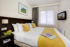 A bed or beds in a room at Citadines Sainte Catherine Brussels