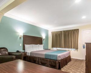 A bed or beds in a room at Rodeway Inn & Suites