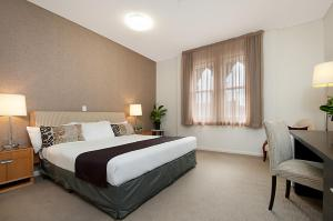 A bed or beds in a room at Adabco Boutique Hotel Adelaide