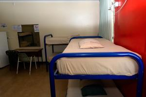 A bed or beds in a room at Palm Court Backpackers