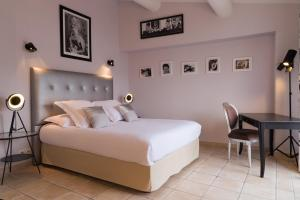 A bed or beds in a room at Mas des Romarins, The Originals Relais (Relais du Silence)