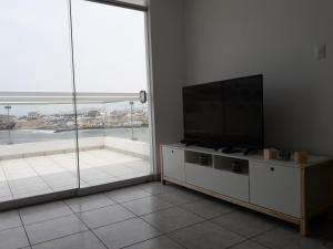 A television and/or entertainment centre at Cozy & elegant apartment with a stunning view to sea