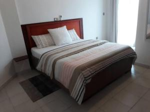 A bed or beds in a room at Le Buffle Noir Appart d'hôtes Douala