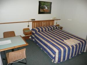 A bed or beds in a room at Hermitage Motel