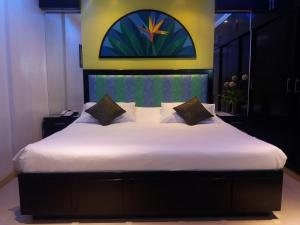 A bed or beds in a room at Fields Walking Street Hotel