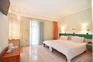 Ένα ή περισσότερα κρεβάτια σε δωμάτιο στο Poseidon Hotel And Apartments