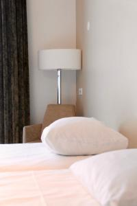 A bed or beds in a room at Parkhotel Valkenburg