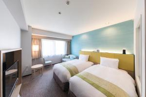 A bed or beds in a room at Holiday Inn Osaka Namba, an IHG Hotel
