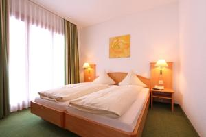 A bed or beds in a room at Bernerhof Swiss Quality Hotel