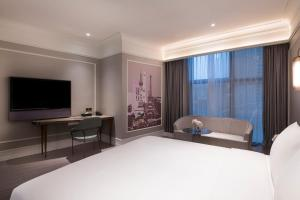 A bed or beds in a room at Mercure Shanghai Yu Garden