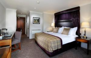 A bed or beds in a room at Macdonald Cardrona Hotel, Golf & Spa
