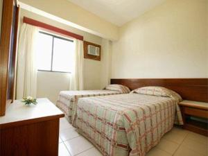 A bed or beds in a room at Residencial Porto Farol