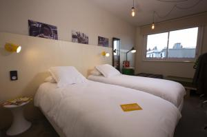 A bed or beds in a room at ARTYSTER CLERMONT-FERRAND