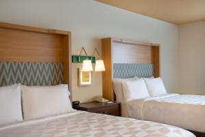 A bed or beds in a room at Holiday Inn Denver East