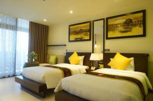 A bed or beds in a room at Villa Hue Hotel