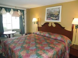 A bed or beds in a room at Budget Inn Watkins Glen