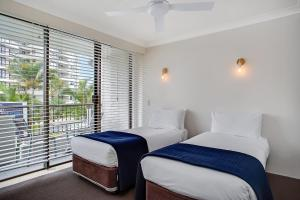 A bed or beds in a room at Broadbeach Pacific Resort