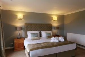 A bed or beds in a room at Stoke By Nayland Hotel, Golf & Spa