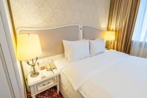 A bed or beds in a room at Attache Hotel
