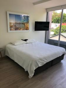 A bed or beds in a room at Bondi Beach Studio King Suite + Balcony