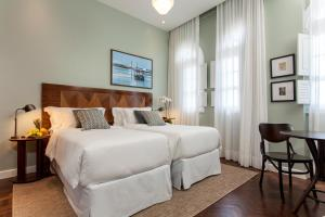A bed or beds in a room at Fera Palace Hotel