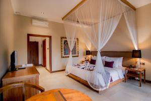 A bed or beds in a room at Ulun Ubud Resort