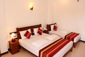 A bed or beds in a room at Mirissa Dive Resort
