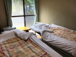 A bed or beds in a room at Minshuku Nodoka