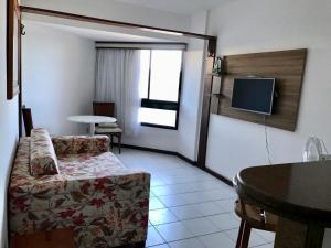 Uma TV ou centro de entretenimento em Flat Vista Mar em Ótima Localização na Pituba