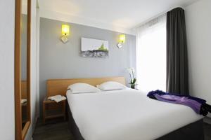 Een bed of bedden in een kamer bij Aparthotel Adagio Access Marseille Prado Périer