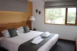 A bed or beds in a room at Lake Crackenback Resort & Spa