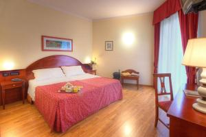 A bed or beds in a room at Recina Hotel