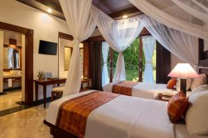 A bed or beds in a room at Bali Tropic Resort & Spa