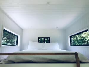 A bed or beds in a room at Francisco d'Anconia Tiny House