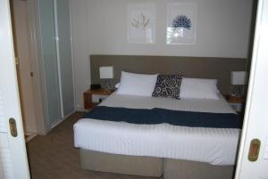 A bed or beds in a room at Absolute Beachfront Scarborough
