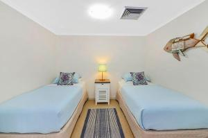A bed or beds in a room at Iluka Retreat Apartments @ Palm Beach