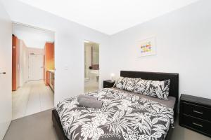 A bed or beds in a room at A Cozy 2BR Suite + Large Balcony at Southern Cross