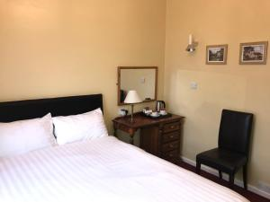A bed or beds in a room at Barons Court Hotel