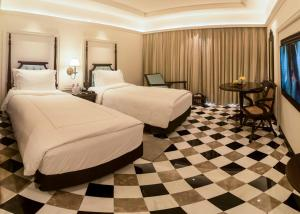 A bed or beds in a room at Taj Bengal