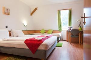 A bed or beds in a room at Alpokalja Panzió Étterem