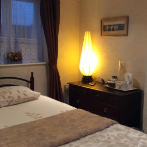 A bed or beds in a room at Hedley Villa Guest House