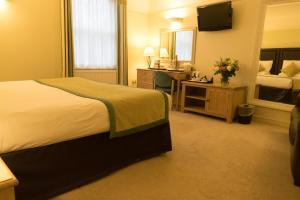 A bed or beds in a room at Stratford Limes Hotel