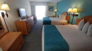 A bed or beds in a room at Tropical Winds Resort Hotel