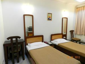 A bed or beds in a room at Hotel Tara Palace, Chandni Chowk