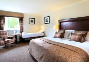 A bed or beds in a room at Macdonald Aviemore Hotel