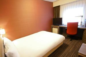 A bed or beds in a room at Daiwa Roynet Hotel Osaka-Yotsubashi